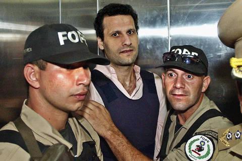 FILE - In this Nov. 17, 2003 file photo, Lebanese citizen Assad Ahmad Barakat, who was then facing tax evasion charges, is escorted by police to a courthouse in Asuncion, Paraguay. On Friday, Sept. 21, 2018, federal police in Brazil arrested Barakat, a fugitive accused of belonging to Lebanon's Hezbollah militia and of being a key financier of terrorism.  (AP Photo/Jorge Saenz, File) ORG XMIT: XLAT117