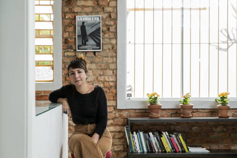 Mulher posa para a foto sentada em um banco alto e apoia o seu braço direito em uma bancada da sala de estar. Atrás dela, há uma janela e uma estante com livros