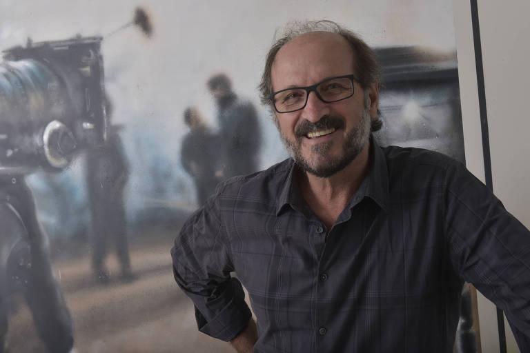Paulo Roberto Schmidt sorri para a câmera e veste óculos e camisa cinza