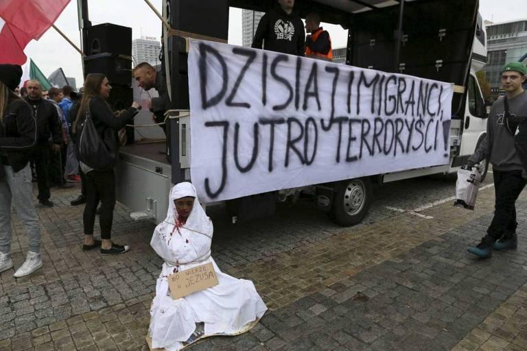 """Faixa com os dizeres """"imigrantes hoje, terroristas amanhã"""" e boneco com roupas árabes são usados em protesto de rua"""