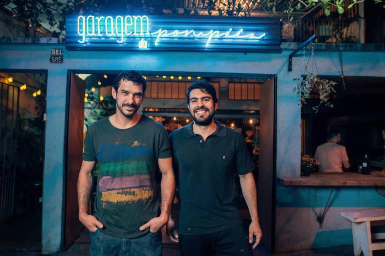 Dois homens de camiseta verde na frente de uma garagem