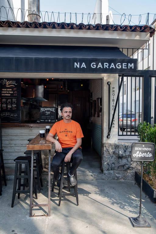 Homem de camiseta laranja sentado em banco na frente de garagem