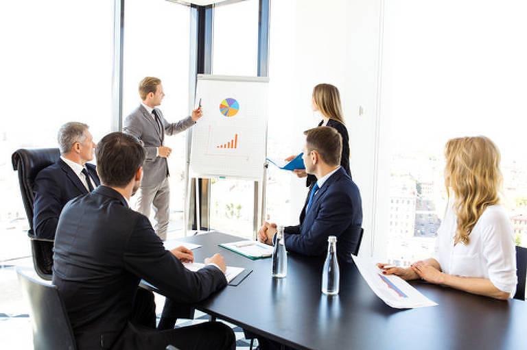 Homem e mulher apresentam gráficos em uma reunião para três homens e uma mulher