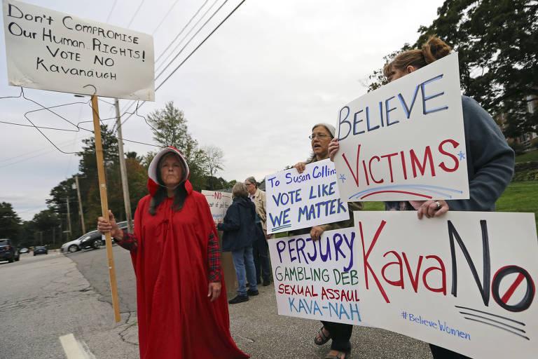 Mulheres carregam cartazes contra juiz. Uma delas usa uma túnica vermelha.