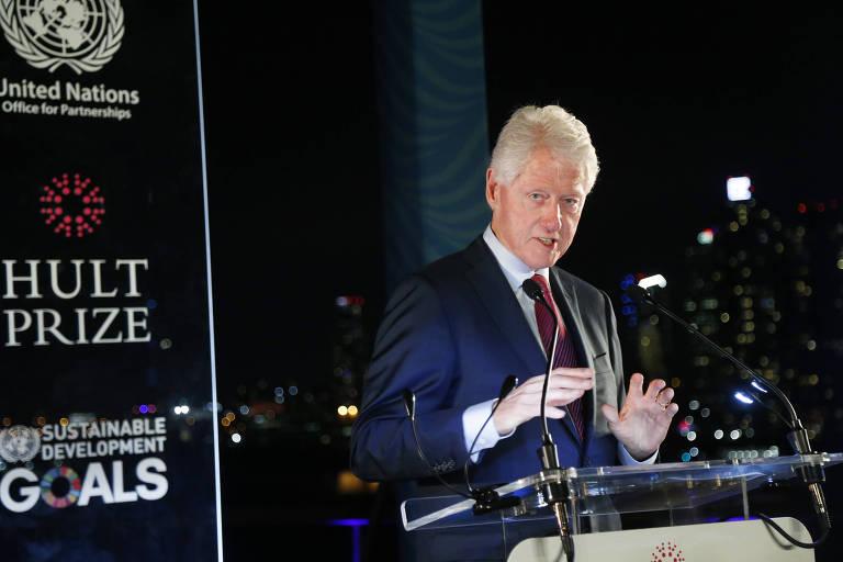 Clinton aparece em um púlpito, com microfone, ao lado do banner