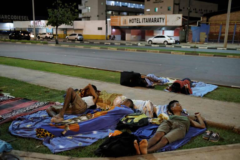 Quatro homens aparecem deitados em colchonetes na calçada; ao fundo, uma avenida de duas pistas
