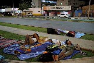 Venezuelan men sleep on the grass in front of interstate Bus Station in Boa Vista