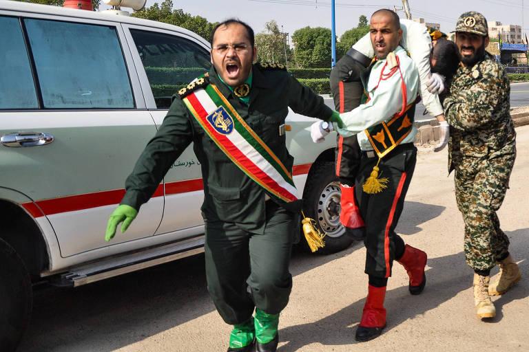 Soldado iraniano carrega um militar morto em ataque a uma parada militar, no Irã