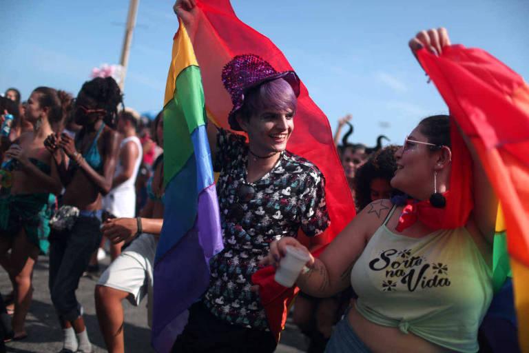 Duas garotas seguram bandeiras com as cores do arco-íris