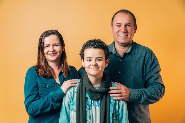 Retrato mostra adolescente em primeiro plano e casal de pais segurando seus ombros