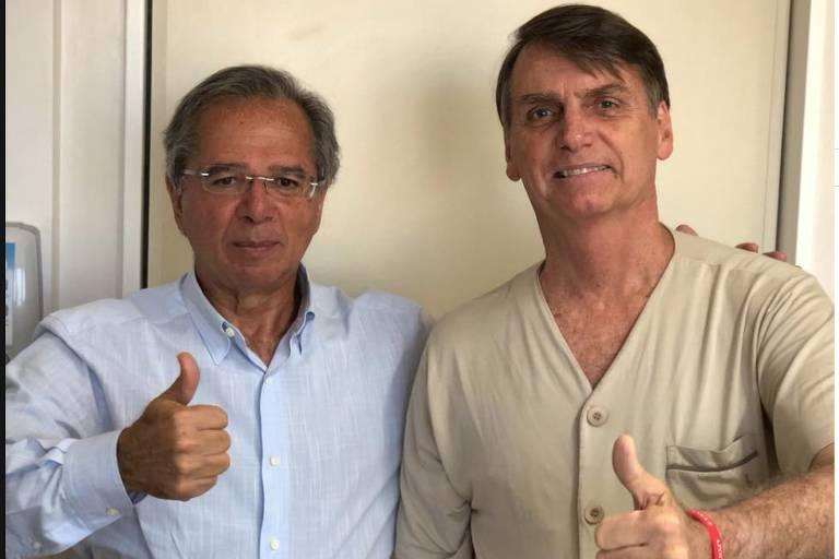 Paulo Guedes e Bolsonaro fazem o sinal de positivo lado a lado