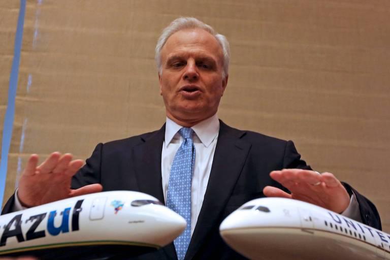 David Neeleman, fundador da Azul, com dois modelos pequenos de avião da marca azul e da United nas mãos