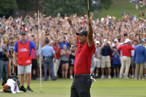Tiger Woods celebrates after picking up his putt for par on the 18th green to win the final round of the Tour Championship golf tournament Sunday, Sept. 23, 2018, in Atlanta. (Hyosub Shin/Atlanta Journal-Constitution via AP) ORG XMIT: GAATJ202