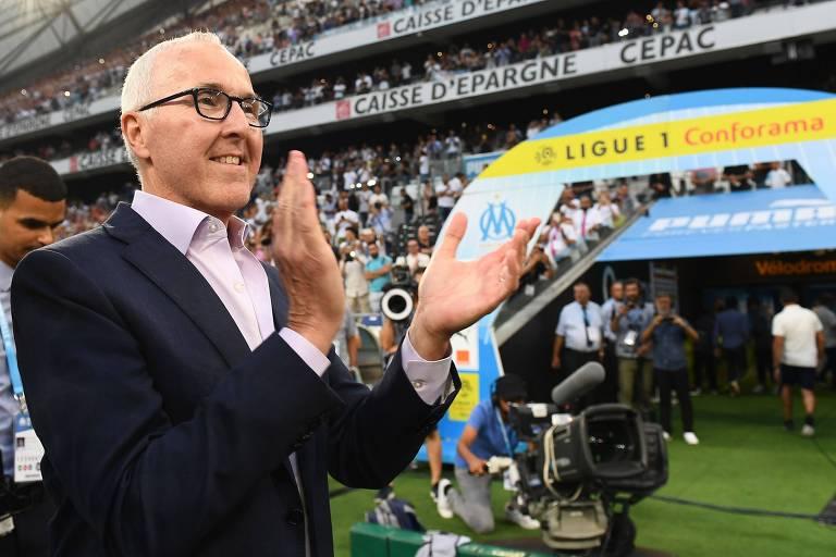 Frank McCourt, proprietário do Olympique de Marselha, caminha e aplaude no estádio da equipe francesa