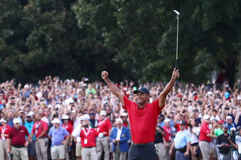 Com torcida ao fundo, Tiger Woods ergue os braços e comemora vitória no domingo (23), sua primeira em cinco anos
