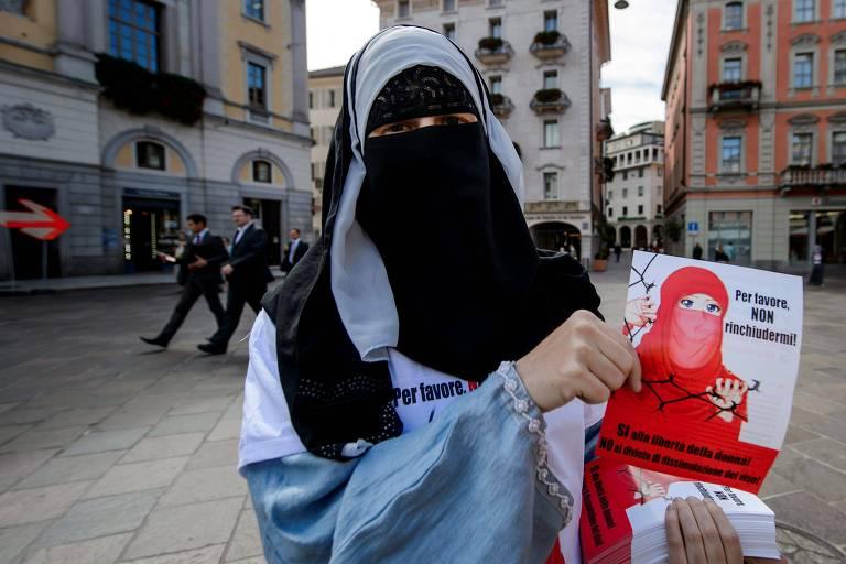 Mulher de véu que cobre  todo o rosto entrega panfletos