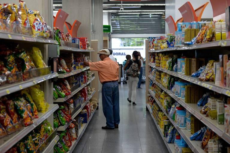 Três pessoas estão em um corredor de um supermercado, com produtos como biscoitos e salgadinhos