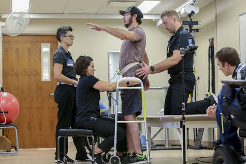 Jered Chinnock stands with the assistance of his therapy team at the Mayo Clinic in Rochester, Minn., on Sept. 18, 2018. Chinnock, paralyzed since 2013, can stand and take steps again thanks to an electrical implant that zaps his injured spine and months of intense rehab as part of a medical study at the clinic. From left are Margaux Linde, Megan Gill, Chinnock, Daniel Veith and Jonathan Calvert. (AP Photo/Teresa Crawford) ORG XMIT: NY911