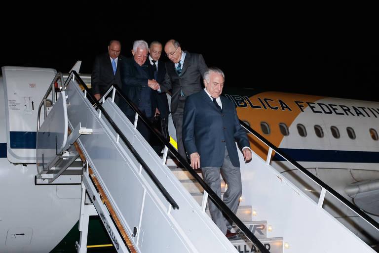 Temer aparece à frente descendo a escada, seguido de quatro ministros e assessores