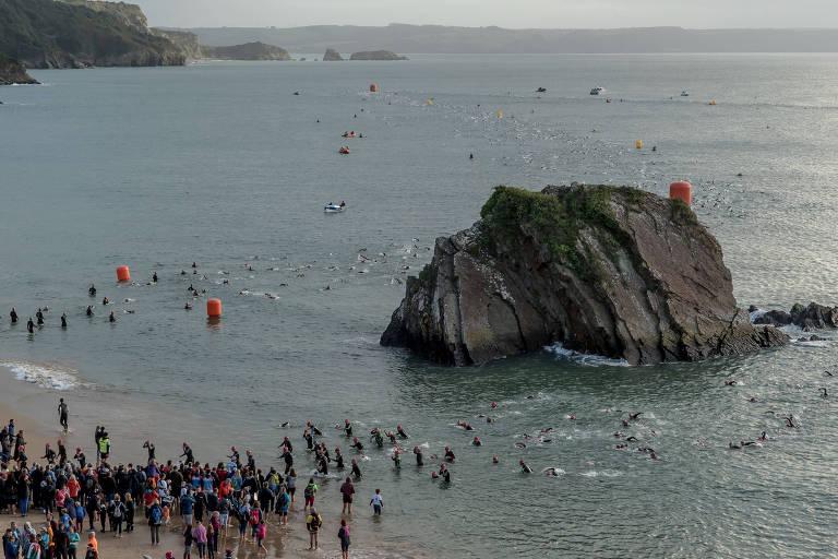 Competidores disputam a prova de natação no Ironman de Tenby, no País de Gales
