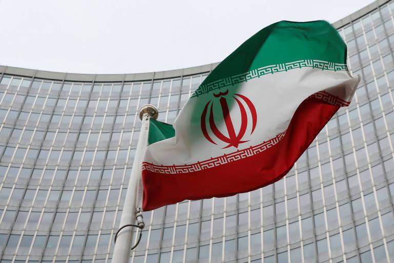 Bandeira iraniana aparece em um mastro à frente de um prédio de vidros espelhados