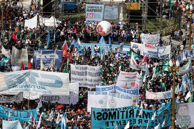 Grupo de manifestantes é visto de cima. Eles carregam faixas de pano.