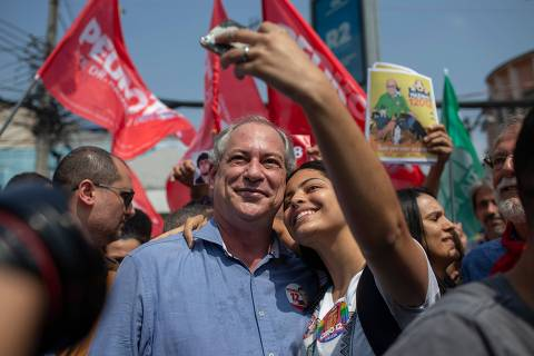 Brazilian Presidential candidate for the Democratic Labour Party, Ciro Gomes (C) poses for a selfie picture with a supporter while campaigning, at Relogio square in the city of Duque de Caxias, Rio de Janeiro state, Brazil on September 25, 2018. (Photo by Mauro Pimentel / AFP)