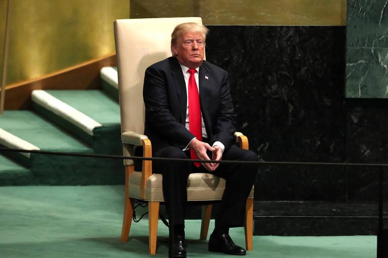 Trump está sentado em uma poltrona de madeira, com encosto de cor bege, no palco da Assembleia-Geral da ONU, que tem um carpete verde. Ao fundo, aparece parte da mesa diretora, de cor preta.