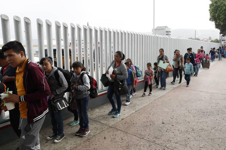 Cerca de 20 pessoas fazem fila ao lado de uma grade. Algumas delas levam crianças pequenas.