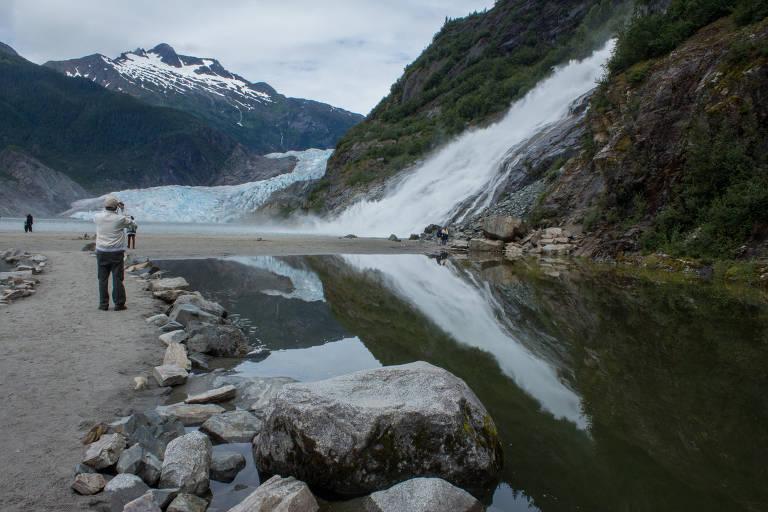 Homem ao lado de pago com cachoeira e geleira ao fundo
