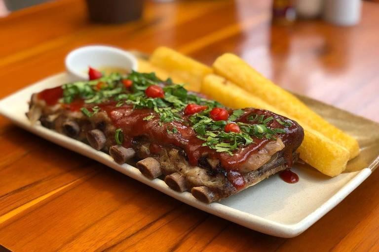 Em uma mesa de madeira, um prato branco acomoda um grande pedaço de costela coberto por goiabada; ao lado, mandioca frita