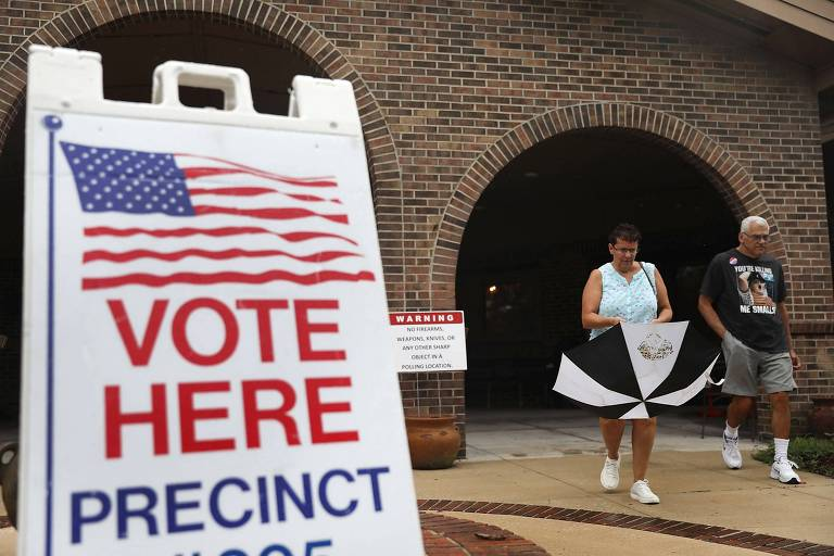 """Uma mulher, que carrega um guarda-chuva, e um homem deixam um prédio de tijolos. À esquerda deles há uma placa com a bandeira americana e a mensagem """"Vote Aqui"""" em inglês."""