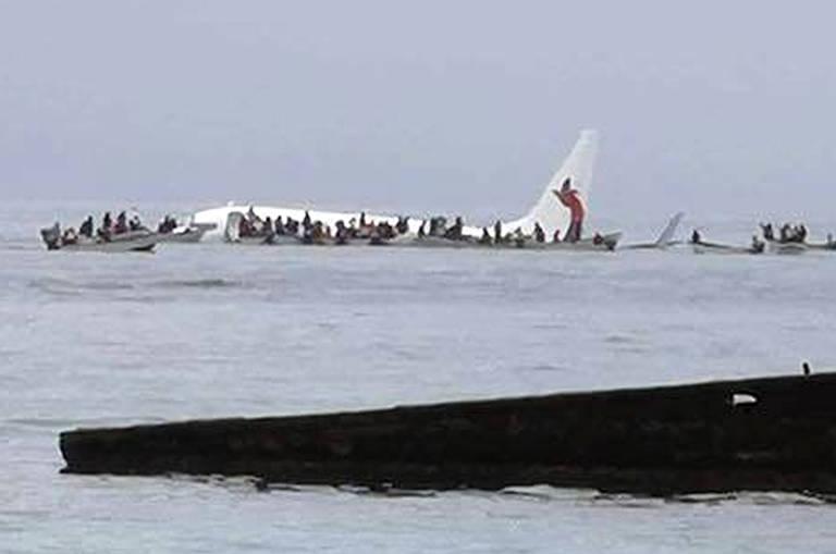 Dezenas de pessoas são retiradas de barco de aeronave semissubmersa em água, vista à distância