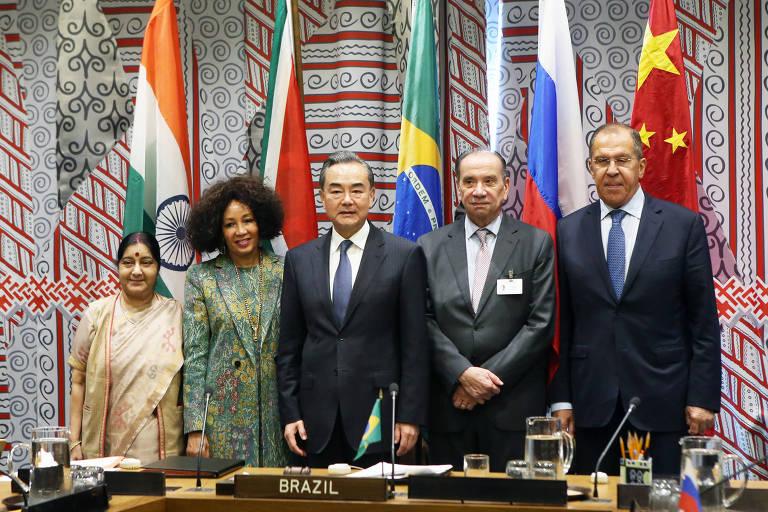 Os cinco chanceleres (a indiana Sushma Swaraj, à esq., a sul-africana Lindiwe Sisulu, o chinês Wang Yi, o brasileiro Aloysio Nunes e o russo Serguei Lavrov) posam atrás de uma mesa e diante de suas respectivas bandeiras