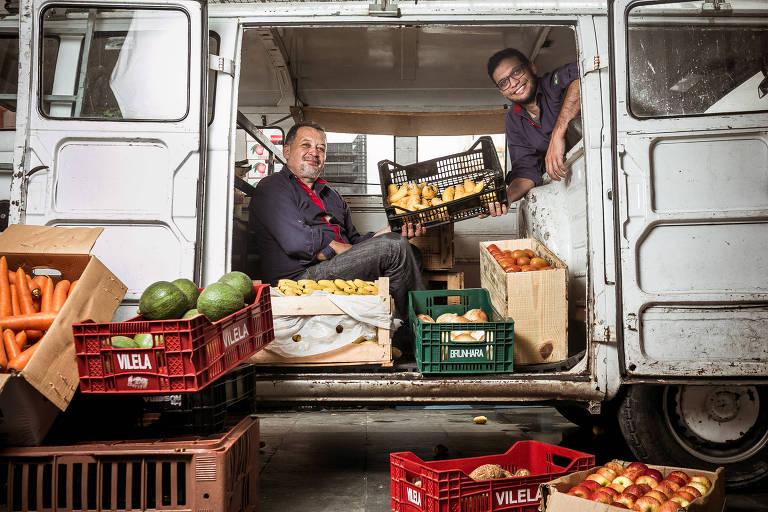 Joaquim e Henrique dentro de uma kombi branca com caixas de frutas e verduras