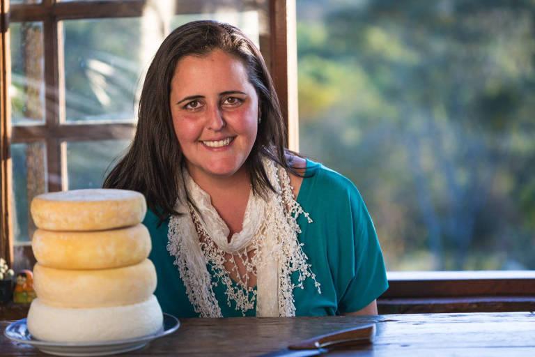 Mariana sentada à frente de uma grande janela à mesa com uma pilha de quatro queijos