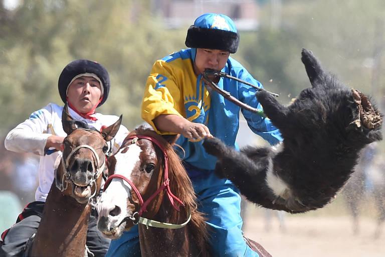 Atletas durante disputa do Kok Boru, espécie de polo a cavalo em que a bola é uma cabra decapitada