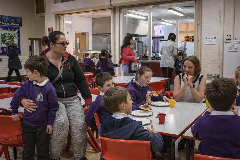 Siobhan Collingwood, head teacher of Morecambe Bay Primary School, joins students for breakfast at the school in Morecambe, England, May 2, 2018. Changes to welfare benefits and funding cuts are driving the working poor into crisis ? and reversing a long-term decline in the childhood poverty rate. (Laura Boushnak/The New York Times)