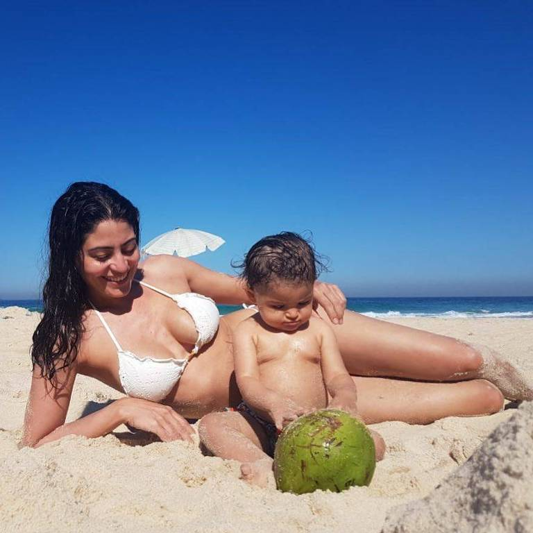 Carol Castro na praia com a filha, Nina, de um ano
