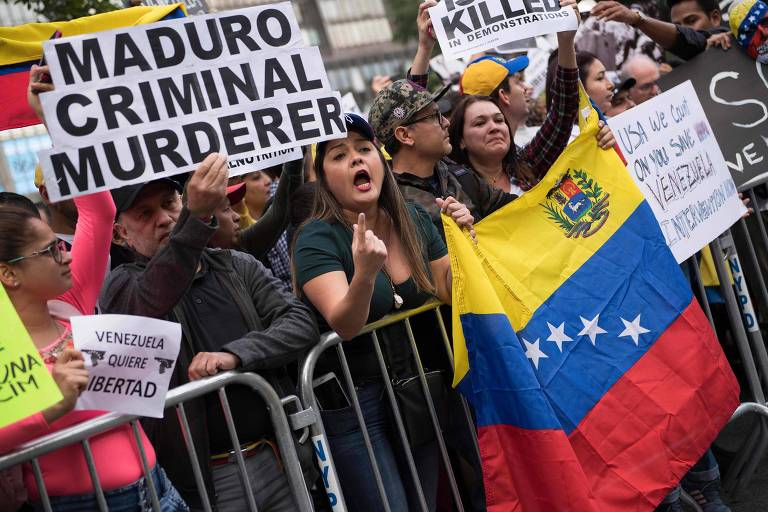 Manifestantes carregam cartazes. Duas mulheres seguram uma bandeira venezuelana escorada em uma grade.
