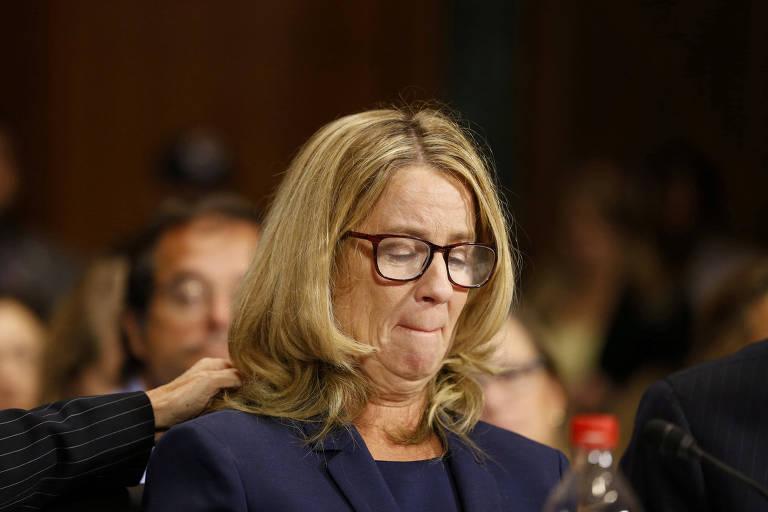 Blasey Ford aparece de olhos fechados e boca franzida. Ela é amparada por uma outra pessoa, que só aparece a mão.