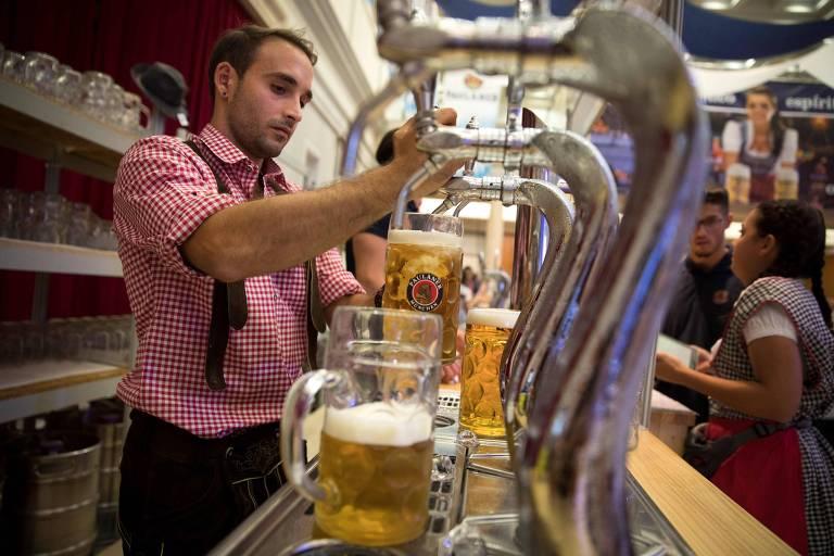Garçom enche copo de cerveja