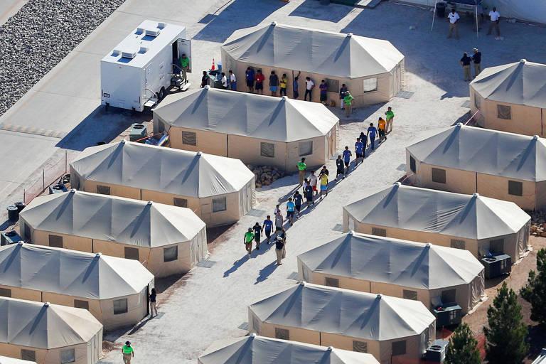 Dez crianças aparecem em fila em um corredor formado no meio entre 12 tendas, seis de cada lado. O local é visto do alto.