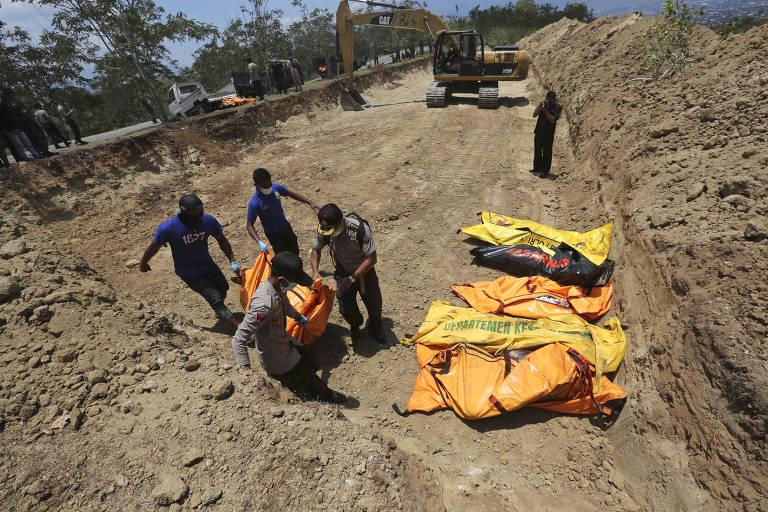 Policiais carregam corpos das vítimas do tsunami durante enterro em massa em vala comum em Palu, na Indonésia