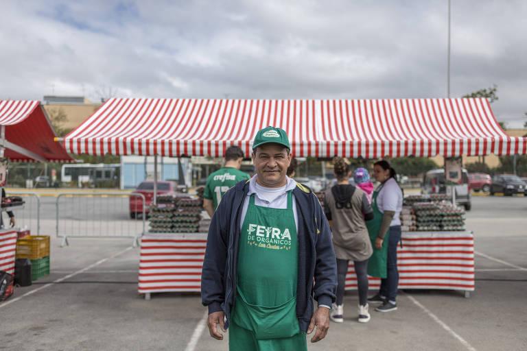 Virgilio Ramos posa para foto, de avental, em frente a uma barraca de feira