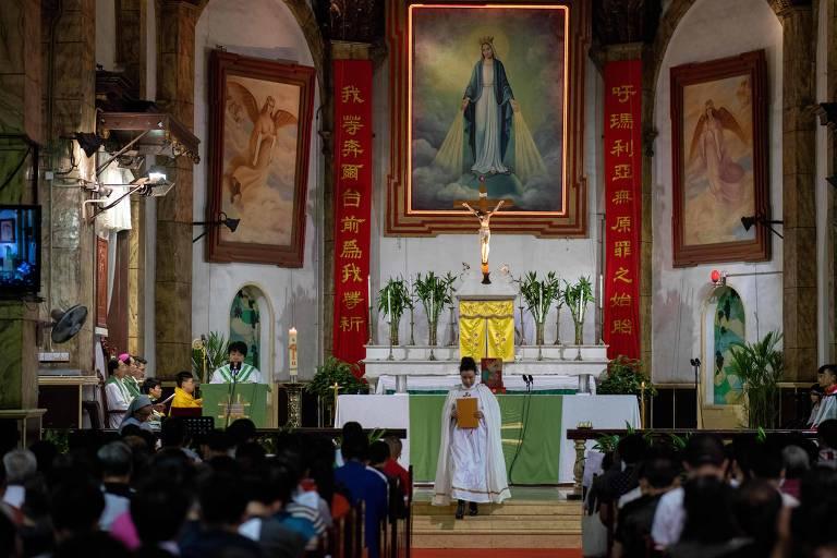 No plano atrás da foto, religioso celebra missa em altar com objetos sagrados e faixas escritas em chinês; na frente, cristãos comparecem à igreja católica sancionada pelo governo chinês, em Pequim