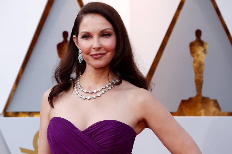 De vestido cor de uva tomara que caia, com os ombros livres, colar e um grande brinco à vista, a atriz posa para foto com mãos na cintura; atrás, uma estatueta do Óscar