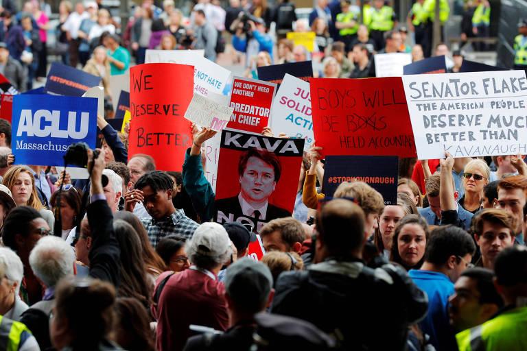 Pessoas seguram uma série de cartazes azuis, vermelhos e brancos com dizeres contra o juiz Brett Kavanaugh em frente à Suprema Corte contra