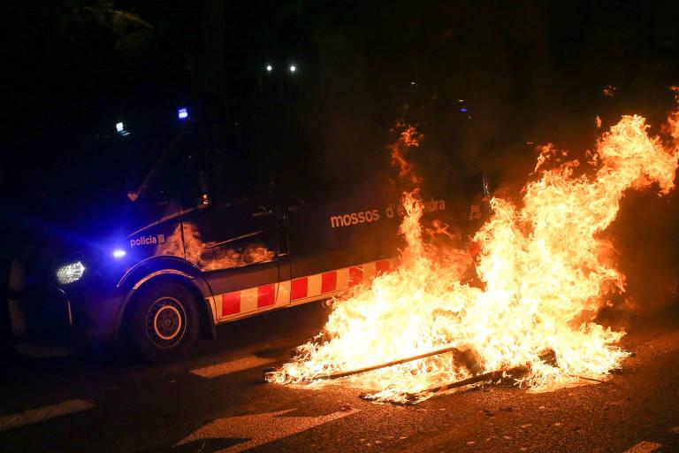 Carro policial de cabeça para baixo em chamas durante protestos na Catalunha