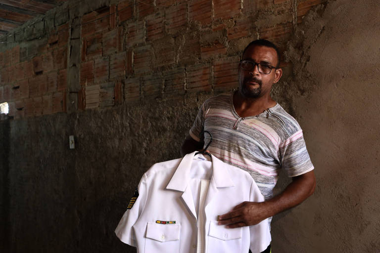 Homem negro segura uniforme branco da Marinha com a mão direita